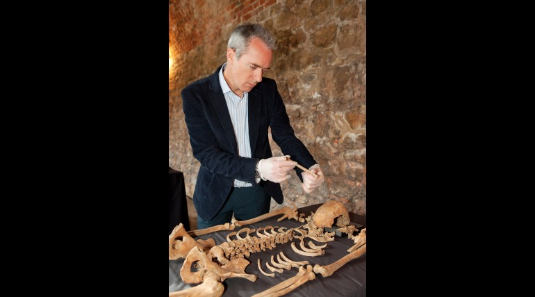 Crossrail Lead archaeologist Jay Carver inspects a rib bone of a Black Death victim in Charterhouse_